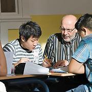Nederland Rotterdam 23-09-2009 20090923 Foto: David Rozing  Serie over onderwijs, het Libanon Lyceum Kralingen,  openbare scholengemeenschap voor mavo, havo en vwo.   Lesuur wiskunde. Een leraar behandelt de leerstof, geeft uitleg aan een groepje leerlingen tijdens het zelfstandig klassikaal werken.  Lesuur wiskunde.   , toelichten, toelichting geven, uitleg, uitleg geven, uitleggen, vaardigheden, vaardigheid, values, voor de klas staan, voortgezet, vut, writing, young, Youth, zachte sector, zelfstandig werken  , , scholengemeenschap, scholier, scholieren, scholing, school, schoolbank, schoolbankje, schooljaar, schoolprestaties, schools, schoolse, schoolse situatie, schrift, schriftelijk, schriftelijke, schrijven, senior, senioren, seniors, student, students, studeren, studie, studieboek, studies, studieuur, study, studying, teacher, teaching, tekst, the netherlands, toekomst, vinger in de lucht houden, vinger in de lucht steken, vinger opsteken, vragen                                                   .Foto: David Rozing