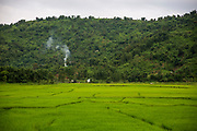 Smoke billows out from a building hidden in the side of a wooded hill above a large paddy field near Nongpoh, Ri-Bhoi district, Meghalaya, India. (photo by Andrew Aitchison / In pictures via Getty Images)