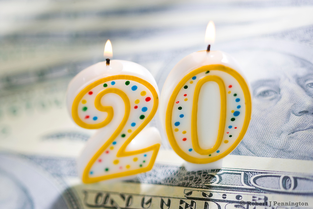 Twenty (20) year celebration candle on U.S. currency.