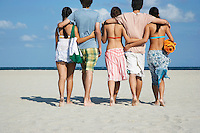 Group of teenagers (16-17) walking on beach back view