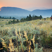 Unidentified riders head down local Singletrack near Jackson, Wyoming while the sunsets through wildfire smoke.