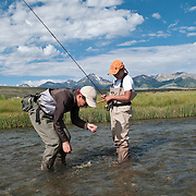 Andy Nelson, 13, helps his brother Nate, 11, catch a rainbow trout on Birch Creek, Idaho.,