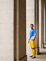 Soccer player holding ball standing in portico portrait