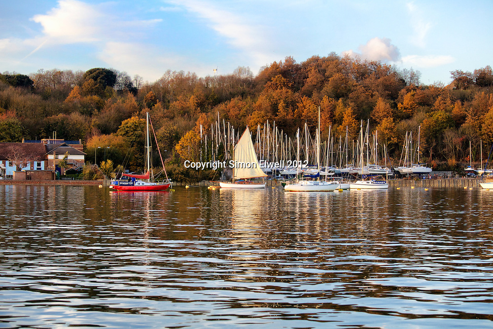 Sailing boat on the river Medway with other boats on moorings