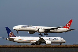 Boeing 777-3F2(ER) (TC-JJI) operated by Turkish Airlines landing past Boeing 787-9 Dreamliner (N27957) operated by United Airlines at San Francisco International Airport (KSFO), San Francisco, California, United States of America