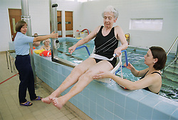 Patient being lifted by hoist from hydrotherapy pool; with physiotherapist,