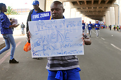 "JOHANNESBURG, SOUTH AFRICA – APRIL 07: A man  kneels with a placard reading ""Gwede, Ciryl Ramaphosa, don't be afraid of Zuma"" as DA (Democratic Alliance) supporters march in protest as part of a nationwide call for President Zuma to step down, in Johannesburg, South Africa, 07 April 2017. Businesses closed and South Africans from numerous political, religious, labour and civic groups gathered at central points across the entire country protesting against President Zuma's recent government reshuffle appointing 10 new ministers and 10 new deputy ministers including the axing of the finance minister. Photo: Dino Lloyd"