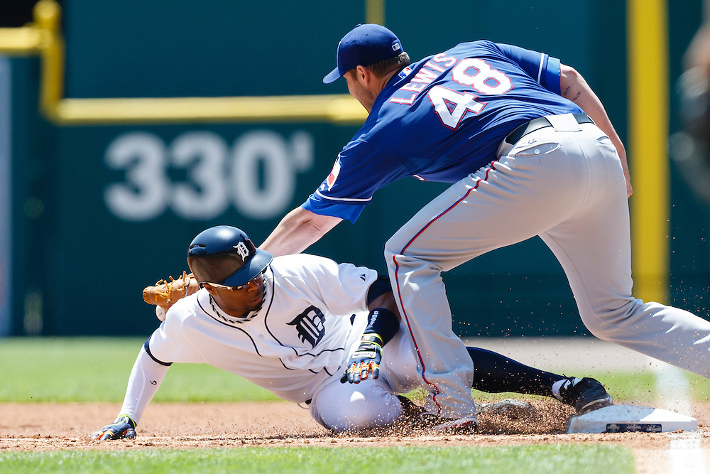 May 25, 2014; Detroit, MI, USA; Detroit Tigers left fielder Rajai Davis (20) slides back to first safe ahead of the throw to Texas Rangers starting pitcher Colby Lewis (48) after he hits a single in the first inning at Comerica Park. Mandatory Credit: Rick Osentoski-USA TODAY Sports