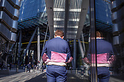 A City worker's jacket lifts in the wind with modern architecture of Leadenhall where many insurance brokers and companies are grouped near Lloyds of London (left) in the City of London, (aka The Square Mile) the capital's financial district, on 3rd September 2019, in London, England.