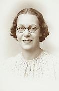 vintage formal studio portrait of an adult female person wearing glasses