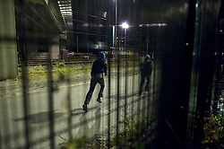 © Licensed to London News Pictures. 09/08/2015. Calais, France. Migrants run as they access the train tracks to the Eurotunnel terminal at Frethun near Calais, northern France. Hundreds of migrants attempt to illegally access the Eurotunnel complex each night in order to board a train and reach the UK. Photo credit: Ben Cawthra/LNP