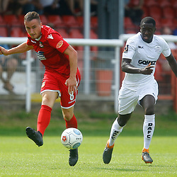 Wrexhams midfielder Luke Young makes a pass whilst shadowed by Dovers midfielder Nortei Nortey during the opening National League match between Dover Athletic and Wrexham FC at Crabble Stadium, Kent on 04 August 2018. Photo by Matt Bristow.