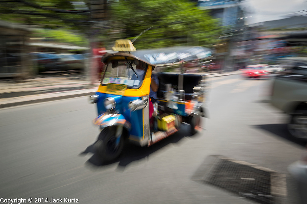 "15 JULY 2014 - BANGKOK, THAILAND: A ""tuk-tuk"" or three wheeled taxi, in Siam Square, a shopping and entertainment area in Bangkok. There is a range of shops and services, including tutor schools, restaurants, cafe, designer clothing boutiques, record stores, bookshops, Hard Rock Cafe and banks in the area. Siam Square is owned by Chulalongkorn University and is managed by its Property Management Office, known as the Chula Property.    PHOTO BY JACK KURTZ"