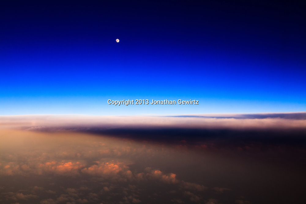 Aerial view of the moon rising over clouds illuminated by the last rays of the setting sun. WATERMARKS WILL NOT APPEAR ON PRINTS OR LICENSED IMAGES.