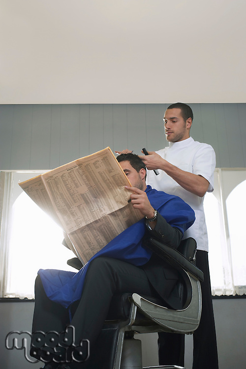 Business man reading newspaper barber cutting hair in barber shop