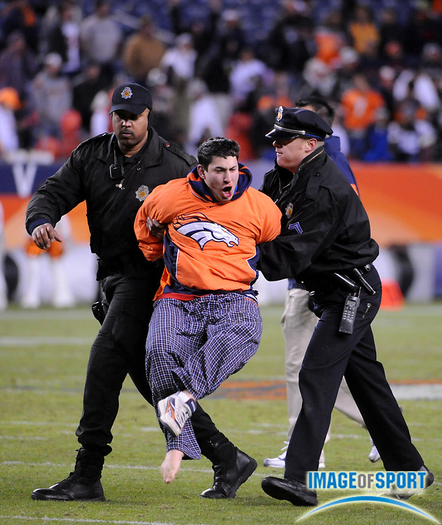 Nov 23, 2008; Denver, CO, USA; A Denver Broncos fan is arrested by police officers after running on the field during game against the Oakland Raiders at Invesco Field.