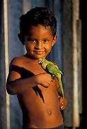 Kid holding Parakeet near Fazenda Sao Franzisco, Ilha do Marajo, Amazon Delta, Amazonia, Brazil
