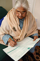 South Asian lady filling in a form,