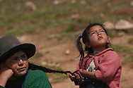 A young girl braids her mother's hair during a community meeting in Andahuaylas, Peru. Sara A. Fajardo