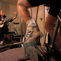 USA, U of W Oceanography grad student plays banjo in workout room aboard R/V Thomas G. Thompson in North Pacific