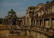 This is a portion of the main gate of the Angkor Wat temple complex, the world's largest single religious monument built for the king Suryavarman II in the early 12th century as his state temple and capital city.<br /> <br /> It is a massive three-tiered pyramid crowned by five lotus-like towers rising 65 meters from ground level is surrounded by a moat and an exterior wall. All the walls of the temple are covered inside and out with bas-reliefs and carvings. <br /> <br /> The ruins of Angkor, a UNESCO World Heritage Site with temples numbering over 1000, are hidden amongst forests and farmland to the north of the Tonle Sap Lake outside the modern city of Siem Reap, Cambodia. <br /> <br /> Angkor Wat has remained a significant religious centre since its foundation--first Hindu, dedicated to Vishnu, then Buddhist. Quite a few of the temples at Angkor have been restored and represent a significant site of Khmer architecture.