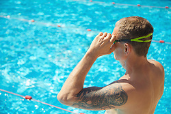 Mature Man Standing by Swimming Pool Adjusting Goggles
