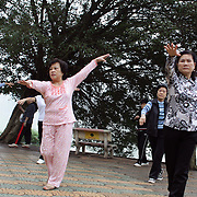 A group of elderly women perform Tai Chi during early morning exercise beside Hoan Kiem Lake, Hanoi, Vietnam.. For a county not know for it's sporting prowess, Hanoi, Vietnam's capital, appears to be gripped in a fitness frenzy. Before 6am street corners, parks and lake sides are a hive of activity as keep fit classes, Tai chi and personal exercise regimes are seen in abundance around the city. Particularly noticeable are Women's keep fit classes, often accompanied by loud poor quality western disco beat music as the occupants of the city get fit come rain or shine. Hanoi, Vietnam. 18th March 2012. Photo Tim Clayton
