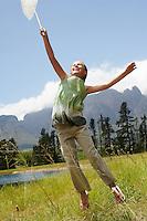 Girl (7-9) in field reaching towards sky with butterfly net.