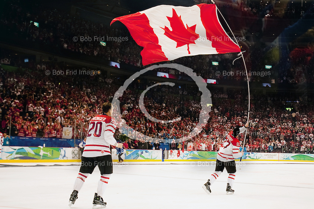 28 February 2010: Canada's Chris Pronger #20 watches teammate Sidney Crosby #87 celebrate their victory by carrying the Canadian flag around the ice at the end of the Gold medal Hockey Final between the United States and Canada during the Vancouver 2010 Winter Olympics  in Vancouver,  British Columbia, Canada.  Final score in Overtime: Canada 3 - USA 2 - Canada wins the Gold Medal and the USA Silver.