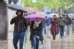 © Licensed to London News Pictures. 10/06/2019. London, UK. Tourists shelter from the rain beneath umbrellas as rain falls in the capital. The Met Office has issued an amber warning for more rain, covering London and parts of southeast England later today.  Photo credit: Dinendra Haria/LNP