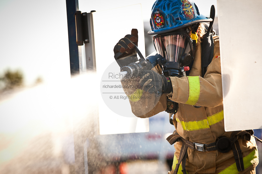 A firefighter aims a firehose at a target while wearing full firefighting gear and working against the clock during the international finals of the Firefighter Combat Challenge on November 18, 2011 in Myrtle Beach, South Carolina.