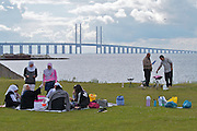 Malmö. Öresund Bridge connects Malmö in Sweden and Denmark's capital Copenhagen, and with its length of 8 kilometers is the longest road and rail bridge in Europe. A muslim family enjoys the spectacular view during their barbacue.