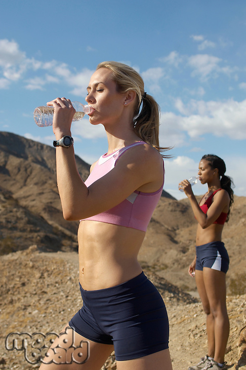 Female joggers drinking from water bottles, in mountains