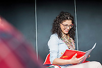 Happy businesswoman reading book in office