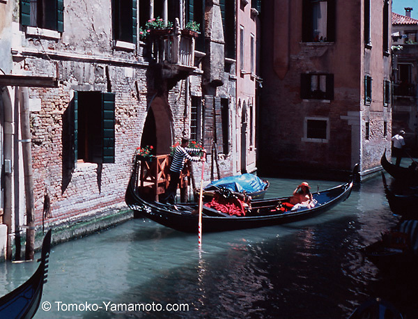 One gondola after another follows in a side canal in Venice, Italy.  The brick fa&ccedil;ade of the building near the central gondola looks old but a wood balcony facing the canal looks freshly painted.  A young woman with a hat on rides in the central gondola rowed by a gondolier in a striped shirt and the next gondola in line is seen by its ferro.  The centra gondola moves through the sunny spot in the center. The woman's hat has a red ribbon and she is wearing pink top and white pants. She is holding down the hat with both of her hands.  The ferro symbolizes six sestieri of Venice with six teeth and a Doge's cap is on top of the teeth. The house behind the central gondola has a Venetian Gothic fa&ccedil;ade. Window boxes with flowers and green shutters add colors to this photo.<br /> This photo has been cropped to emphasize the central gondola, but the original shows the entire Venetian Gothic fa&ccedil;ade of three windows above the flower boxes. Photo of Venice, Italy by Tomoko Yamamoto. Original on 35mm slide film. Foto der Gondelfahrt im Seitenkanal in Venedig, Italien.  Venezia, Italia.