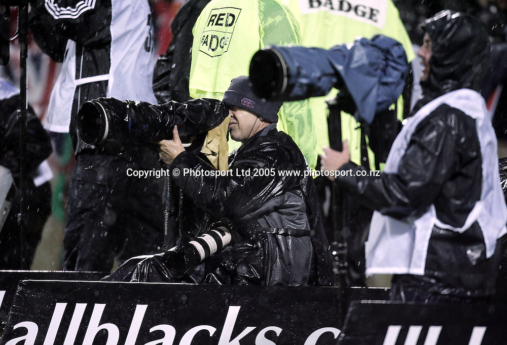 Photoport Photographer Andrew Cornaga weathers the rough conditions during the 1st test match between the New Zealand All Blacks and the British and Irish Lions at Jade Stadium in Christchurch, New Zealand on Saturday 25 June, 2005. The All Blacks won 21-3. Photo: Anthony Phelps/PHOTOSPORT<br />