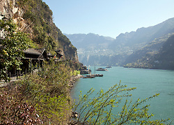 View of the Yangtze River at Hama Spring, Mingyue Bay, between Jingzhou and Chongqing. Building and dock are part of a re-created water village,a shore excursion stop for river cruises.