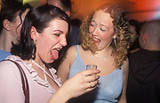 A girl pulling a face and sticking her tongue out after drinking a shot, UK 2004