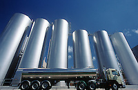 Milk transport truck parked alongside storage tanks