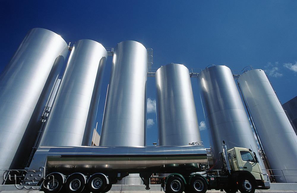 Milk transport truck parked alongside storage tanks