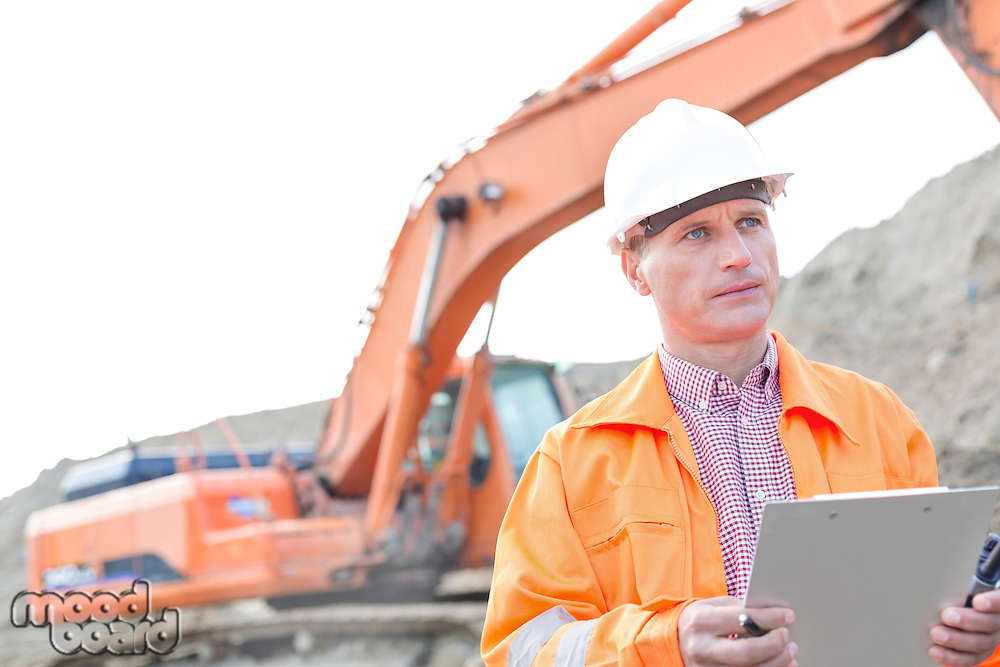 Supervisor looking away while holding clipboard at construction site