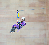 Minneapolis, MN - January 26, 2017: Bold North Zip Line rider wearing a purple unicorn costume, zooms down the line and over the Mississippi River as part of the SuperBowl LII events taking place in Minneapolis.