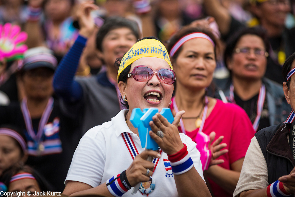 "15 NOVEMBER 2013 - BANGKOK, THAILAND: An anti-government protester applauds during a protest rally in Bangkok. Tens of thousands of Thais packed the area around Democracy Monument in the old part of Bangkok Friday night to protest against efforts by the ruling Pheu Thai party to pass an amnesty bill that could lead to the return of former Prime Minister Thaksin Shinawatra. Protest leader and former Deputy Prime Minister Suthep Thaugsuban announced an all-out drive to eradicate the ""Thaksin regime."" The protest Friday was the biggest since the amnesty bill issue percolated back into the public consciousness. The anti-government protesters have vowed to continue their protests even though the Thai Senate voted down the bill, thus killing it for at least six months.      PHOTO BY JACK KURTZ"