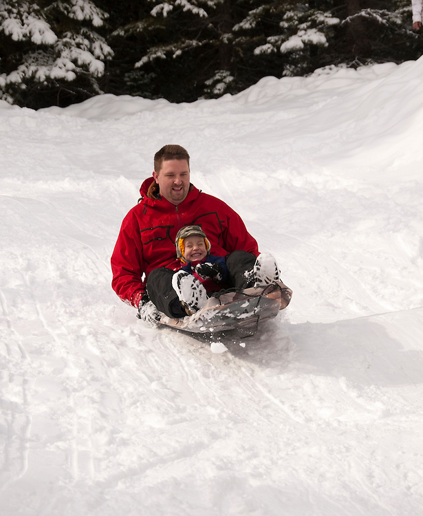 California, Lake Tahoe: Child and father enjoy snow play with sled at North Lake Tahoe Regional Park.  Photo copyright Lee Foster.  Photo # cataho107629