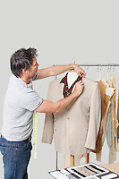 Male dressmaker adjusting suit on tailor's dummy in design studio