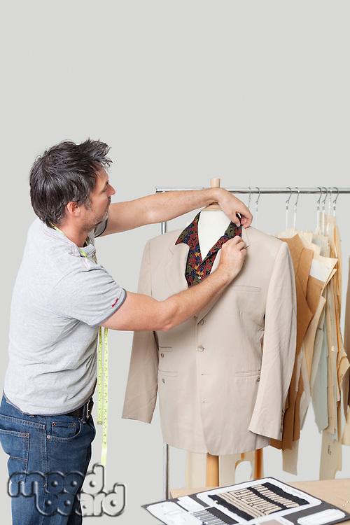 Male dressmaker adjusting suit on tailor's dummy in design studio