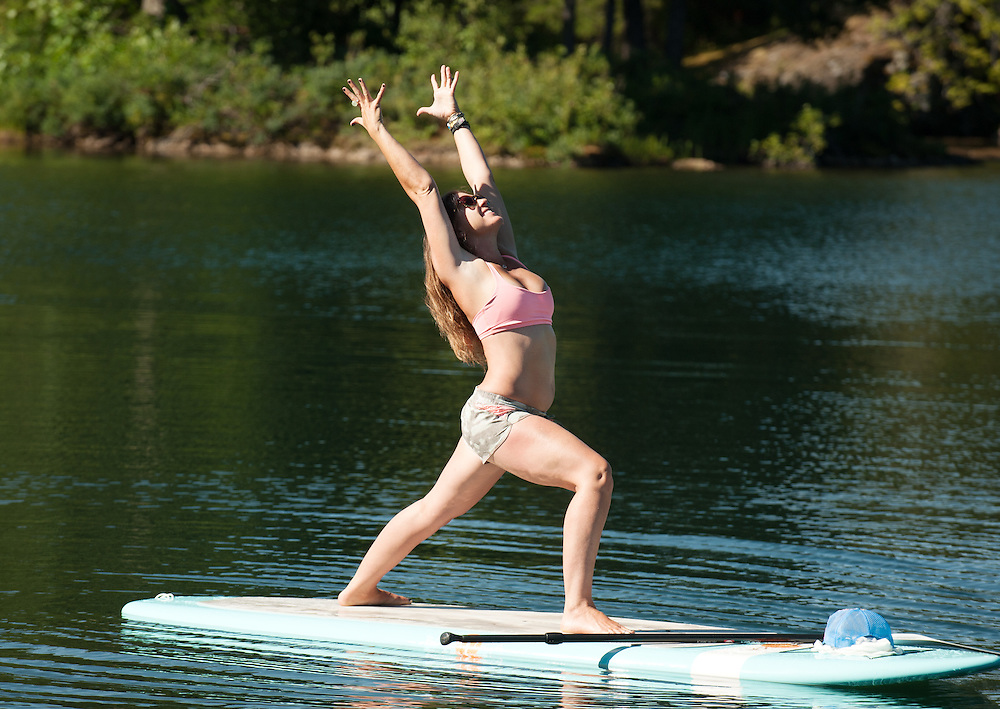 Yoga instructor Jenn Perell of Yoga on Liquid does a stand up paddle board yoga pose on Alpha Lake.  Friday, August 1st, 2014.<br /> <br /> Photo Credit: David Buzzard
