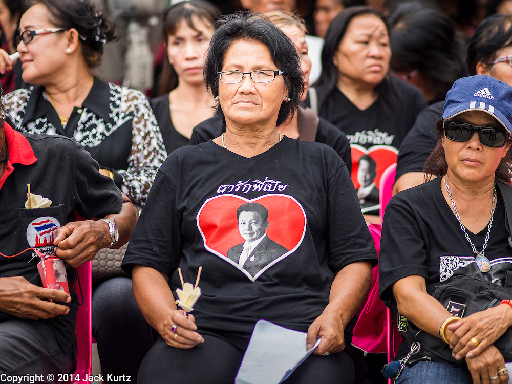 19 OCTOBER 2014 - BANG BUA THONG, NONTHABURI, THAILAND: A mourner wearing a tee shirt with Apiwan's photo on it at Apiwan Wiriyachai's cremation at Wat Bang Phai in Bang Bua Thong, a Bangkok suburb, Sunday. Apiwan was a prominent Red Shirt leader. He was member of the Pheu Thai Party of former Prime Minister Yingluck Shinawatra, and a member of the Thai parliament and served as Yingluck's Deputy Prime Minister. The military government that deposed the elected government in May, 2014, charged Apiwan with Lese Majeste for allegedly insulting the Thai Monarchy. Rather than face the charges, Apiwan fled Thailand to the Philippines. He died of a lung infection in the Philippines on Oct. 6. The military government gave his family permission to bring him back to Thailand for the funeral. His cremation was the largest Red Shirt gathering since the coup.     PHOTO BY JACK KURTZ