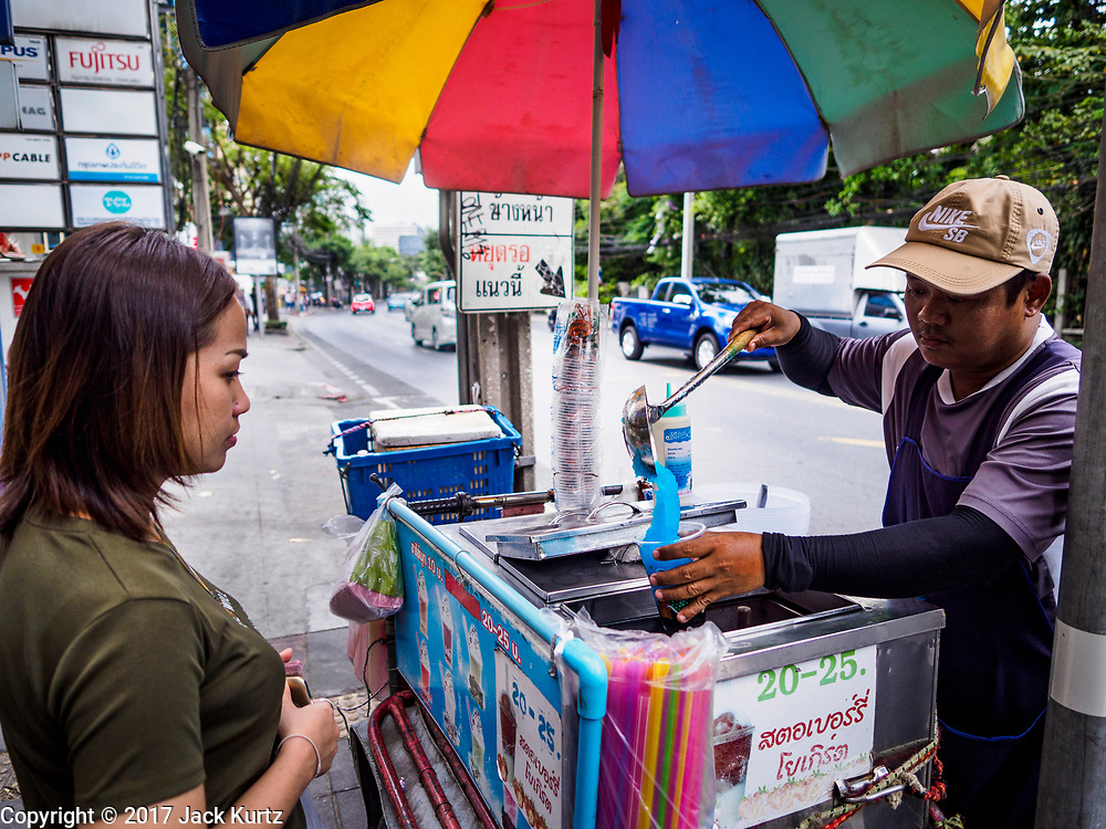 24 MARCH 2017 - BANGKOK, THAILAND: People walk past street food carts on Sukhumvit Soi 63 (Ekkamai) in the neighborhood carts are being evicted from. Food cart vendors along Sukhumvit Road between Sois 55 (Thong Lo) and 69 (Phra Khanong) in Bangkok have been told by city officials that they have to leave the area by 17 April. It's a part of an effort by Bangkok city government, supported by the ruling junta, to take back the city's sidewalks. The evictions in the area are the latest in mass evictions of Bangkok street food vendors after similar actions elsewhere on Sukhumvit, in the Ari area, in Silom/Patpong and Ratchaprasong neighborhoods. The vendors in Thong Lo/Phra Khanong are popular with local office workers because most of the formal restaurants in the area serve foreign tourists and upper class Thais and are very expensive. The street food carts serve meals starting at about 35Baht ($1US). The city has not announced if they will provide alternative locations for the carts.     PHOTO BY JACK KURTZ