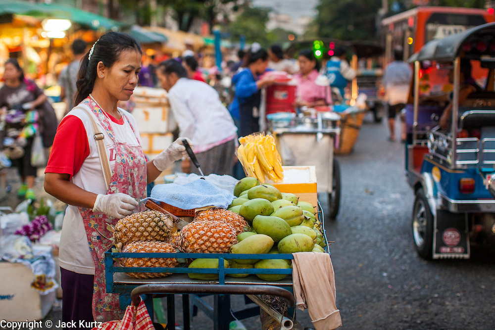19 OCTOBER 2012 - BANGKOK, THAILAND:   A food vendor sells mangos and pineapple from her cart in the Bangkok Flower Market. Early in the day, the market takes over the streets in the area, after about 7AM the streets are fully reopened to traffic. The Bangkok Flower Market (Pak Klong Talad) is the biggest wholesale and retail fresh flower market in Bangkok.  The market is busiest between 3:30AM and 6AM. Thais grow and use a lot of flowers. Some, like marigolds and lotus, are used for religious purposes. Others are purely ornamental.           PHOTO BY JACK KURTZ